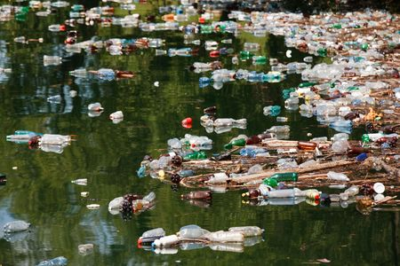 many plastic bottles and other garbage on lake water
