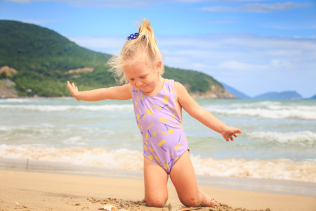 closeup European cute little blond girl with pigtail in swimsuit sits on sand near nice shell against wave surf