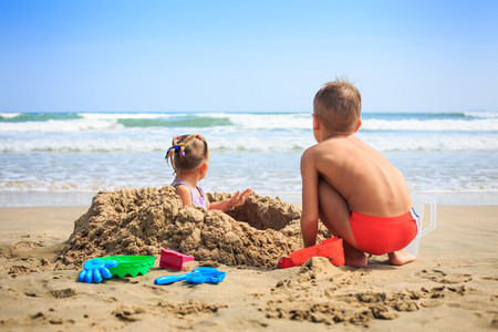 Foto de backside view little blond girl sits in sand hole boy squats near heap and play on beach against ocean - Imagen libre de derechos