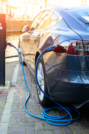 Photo pour Charging modern electric car on the street in rays of the sun. Vehicle Rechargeable Batteries, future of transportation - image libre de droit