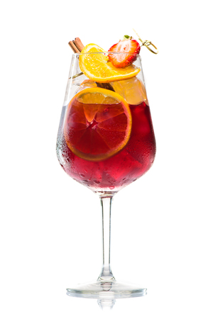 Foto de alcoholic cocktail Jager bomb with cinnamon sticks, strawberry and grapefruit in wine glass isolated on white background - Imagen libre de derechos
