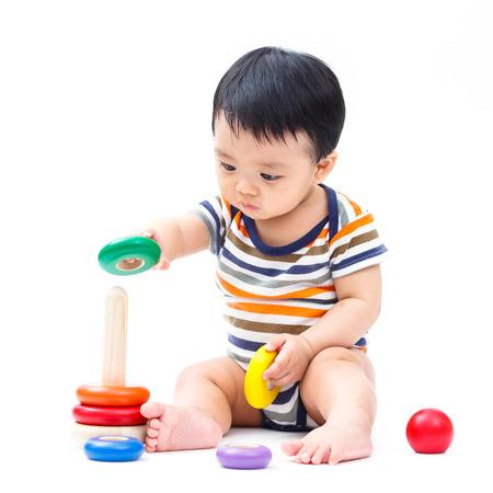 Foto de Cute asian baby playing toy isolated on white - Imagen libre de derechos