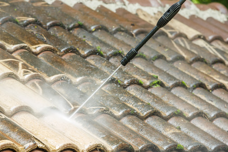 Photo pour Roof cleaning with high pressure water cleaner - image libre de droit