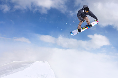 Jumping snowboarder through air on blue sky background