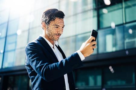 Photo pour Man unloking his smartphone with Face ID system - image libre de droit