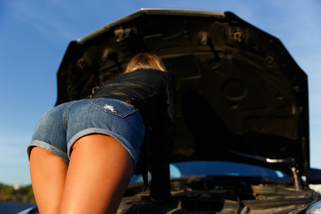 Photo for Image of back of young girl in short shorts mending black car in summer day - Royalty Free Image