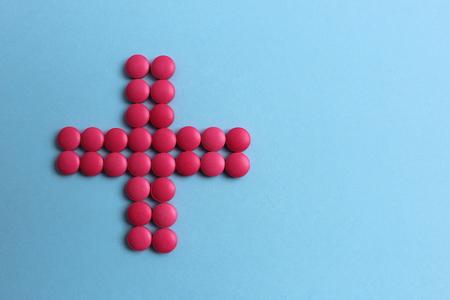Photo pour pink pills lined up with a plus sign - image libre de droit