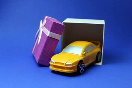 Foto de A toy car comes out of the festive box as a gift - Imagen libre de derechos