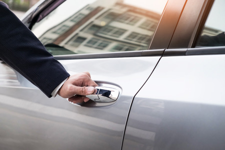 Photo pour Chauffeur s hand on handle. Close-up of man in formal wear opening a passenger car door. - image libre de droit