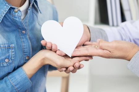 Foto de charity, health care, donation and medicine concept - doctor man hand giving heart to patient - Imagen libre de derechos