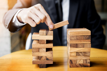 Photo for Planning, risk and wealth strategy in business concept, businessman and insurance gambling placing wooden block on a tower. - Royalty Free Image