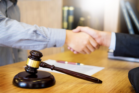 Foto de Gavel Justice hammer on wooden table with judge and client shaking hands after adviced in background at courtroom, lawyer service concept - Imagen libre de derechos