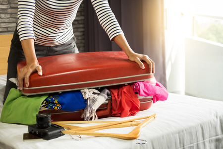 Foto de Woman trying to fit all clothing to packing her red suitcase before vacation - Imagen libre de derechos