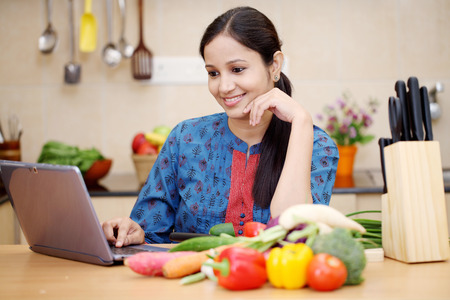 Young Indian woman using a tablet computer in her kitchen