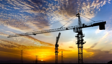 Photo for Industrial construction cranes and building silhouettes over sun at sunrise  - Royalty Free Image