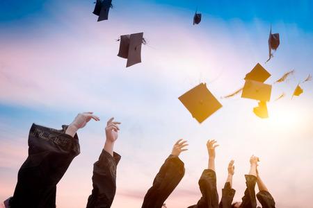 Photo pour graduates throwing graduation hats in the air. - image libre de droit