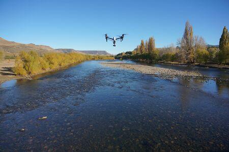 Foto de Inspire quadcopter drone flying over river. (front view) - Imagen libre de derechos
