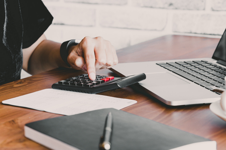Photo pour Business women work with calculator and laptop,pen and notebook on the wooden table - image libre de droit