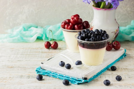 Photo pour Italian pana cota with berry jam and fresh blueberries on a light background - image libre de droit
