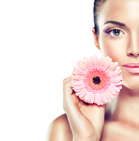 Photo pour Beauty Portrait. Beautiful Spa Woman Touching her Face .  Cosmetics and cosmetology. Clean face , skin care .  girl with delicate flower near the face - image libre de droit