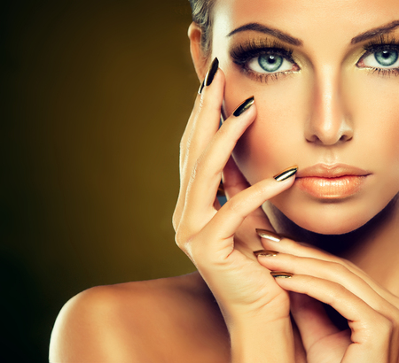 Photo pour Beautiful girl with the Golden makeup and gold  metal nails.  Fashion woman Portrait. - image libre de droit