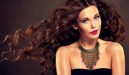 Photo pour Beautiful model brunette with long curled hair and jewelry necklace - image libre de droit