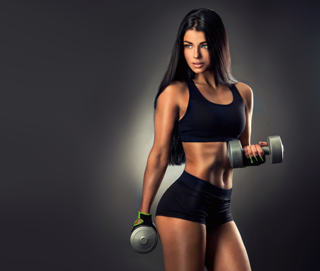 Photo pour Beautiful fitness woman lifting dumbbells . Fitness sporty woman showing her well trained body. - image libre de droit