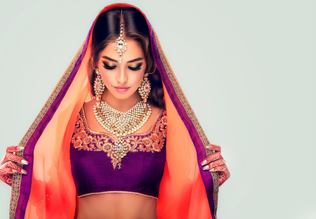 Young hindu woman model with tatoo mehndi and kundan jewelry . Traditional Indian costume lehenga choli .