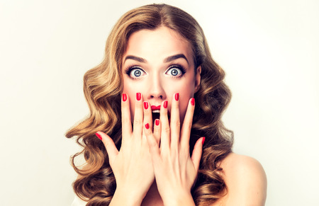 Photo pour Facial expression of young woman displaying  shock, astonishment  and amazement. Beautiful girl with curly hair, perfect mack up and manicure. - image libre de droit