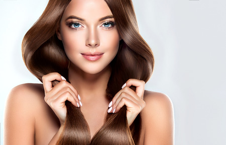 Beautiful model girl with shiny brown straight long hair . Care and hair products.