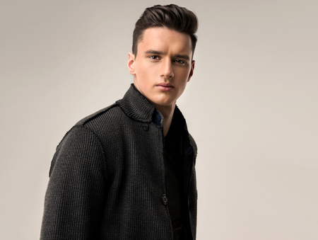 Foto de Portrait of a handsome young man with trendy hairstyle, dressed in a stylish and fashionable wool jacket. - Imagen libre de derechos