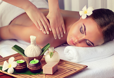 Photo pour Young lady who lays on massage table and gets massage treatment.Spa and  body massage. - image libre de droit