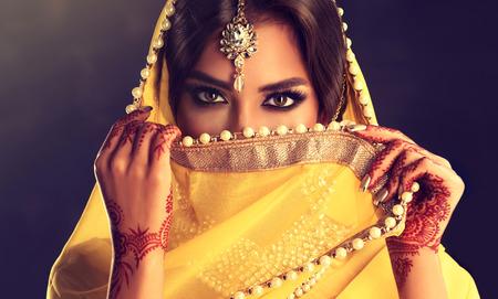 Photo for Beautiful indian girl . Young hindu woman model  with tatoo mehndi  and kundan jewelry . Traditional Indian costume, yellow saree. - Royalty Free Image