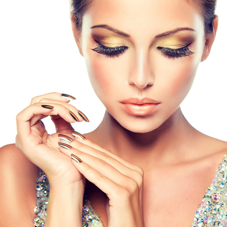 Photo pour Golden make up, bright gilded manicure and elegant gesture. Close up portrait of  attractive woman model. - image libre de droit