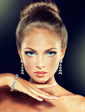Foto de Young charming woman-model, with a hair gathered in a bun and dressed in modern, fashionable jewelry. Examples of different designs for beads, bracelets and earings. - Imagen libre de derechos