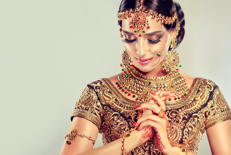 Foto de Young attractive model dressed in posh, gildet, indian costume and Kundan style jewelry. Traditional Indian costume lehenga choli. - Imagen libre de derechos