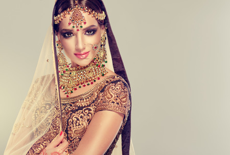 Photo for Young attractive model dressed in posh, gildet, indian costume and Kundan style jewelry. Traditional Indian costume lehenga choli. - Royalty Free Image