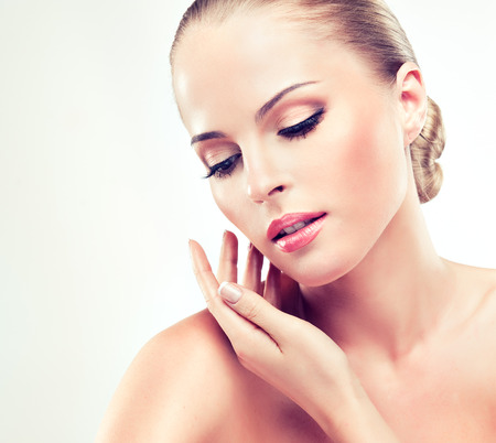 Foto de Beautiful, young, blonde haired woman with clean fresh skin is touching the face. Soft make up and hair gathered in the tuft. Facial treatment, cosmetology , beauty technologies and spa. - Imagen libre de derechos