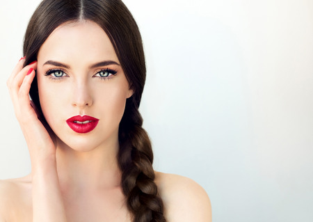 Foto de Close up portrait of beautiful  young brunette woman-model  with  long braided hair. Pigtail hairstyle. Bright blue eyes, red lipstick on the lips and red  manicure on the nails. - Imagen libre de derechos