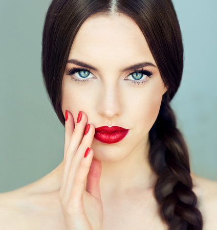 Photo pour Close up portrait of beautiful  young brunette woman-model  with  long braided hair. Pigtail hairstyle. Bright blue eyes, red lipstick on the lips and red  manicure on the nails. - image libre de droit