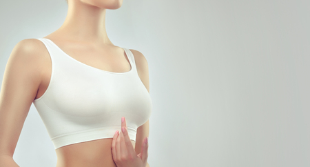 Photo pour White top on the attractive, well shaped woman breast. An example of slender figure for sport, fitness or plastic surgery and esthetic cosmetology. - image libre de droit