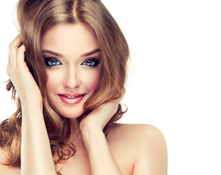 Photo for Young woman is dressed up in a  vivid make up, is touching own face and hair. Attractive woman with face full of emotions. Voluminous, shiny and wavy hair,black eyelashes and  gilded eyelids. - Royalty Free Image