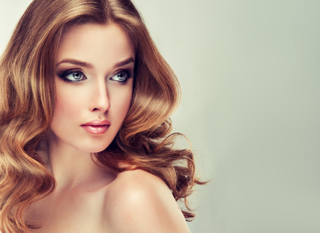 Photo pour Young woman is dressed up in a  vivid make up, is touching own face and hair. Attractive woman with face full of emotions. Voluminous, shiny and wavy hair,black eyelashes and  gilded eyelids. - image libre de droit