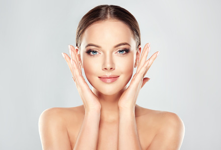 Photo pour Gorgeous, young, brown haired woman with clean fresh skin touchs the face. Facial treatment, cosmetology, beauty technologies and spa. - image libre de droit