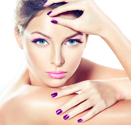 Photo pour Delicate and stylish make up in a light purple color and purple manicure on the nails. Young, attractive woman with clean fresh skin is touching the face. Close up portrait. - image libre de droit