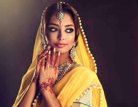 Photo pour Portrait of beautiful indian girl dressed in a traditional national suit-sari,  mehndi henna tattoo is  painted on her hands and traditional kundan style jewelry set. Black haired indian young woman put on  in a posh outfit lehenga choli. - image libre de droit