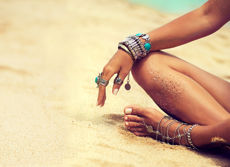 Foto de Woman is sitting in relaxed position on tropical sandy beach. Body parts. Tanned girl in lotus position dressed in silver jewelry,bracelets and rings.Boho style. - Imagen libre de derechos