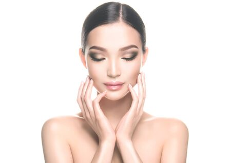 Foto de Gorgeous, young, asian black haired woman with clean fresh skin is touching the face. Oriental beauty. Facial treatment, cosmetology, beauty technologies and spa. - Imagen libre de derechos