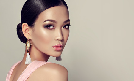 Foto de Young, gorgeous asian fashion-model put on in a smoky eyes style make up, black hair gattered in a beam. dressed in tassel earrings and  pink gown. Oriental beauty. - Imagen libre de derechos