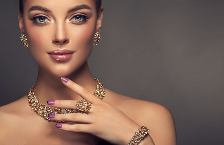 Foto de Beauty portrait of young gorgeous woman is dressed in a jewelry set of necklace, ring and earings. Pretty  blue eyed model is demonstrating an attractive make up and manicure. - Imagen libre de derechos
